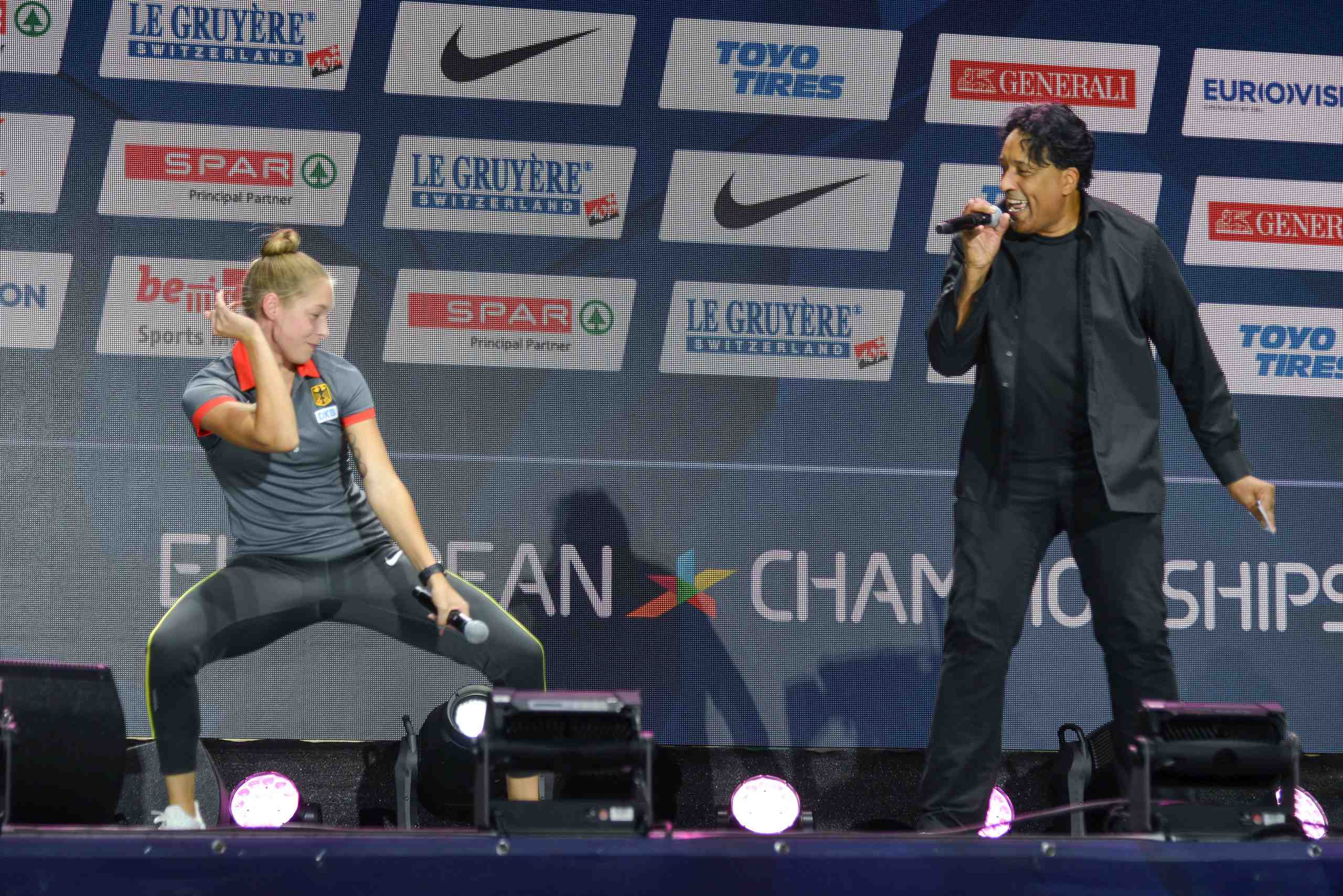 Gina Lückenkemper dances while host Cherno Jobatey raps at the medal ceremony of the European Athletics Champioships 2018